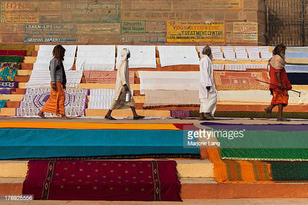 CONTENT] Four men pilgrims and sadhus are walking by the ghats of Benares with colorful linen and saris drying under the sun The scene is reminding...