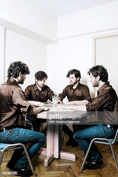 four men playing cards at a round table - cloning stock pictures, royalty-free photos & images