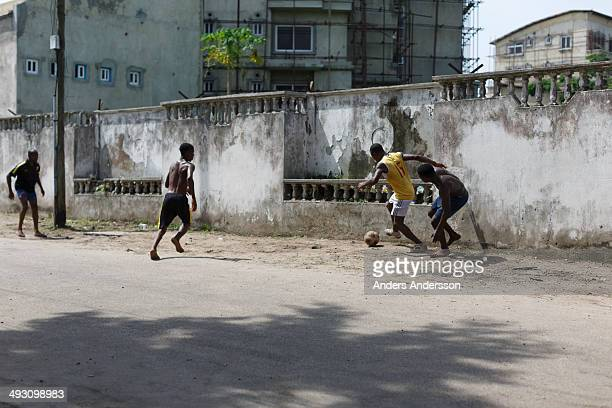 Four men playing football/soccer for fun on a street in Lagos, Nigeria