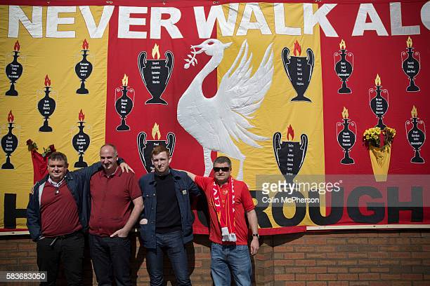 Four men pose for a photograph in front of a banner commemorating the 1989 Hillsborough stadium disaster, before the 25th anniversary memorial...