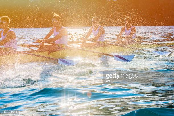 Four men rowing on a lake