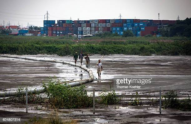 Four men run across a swamp In the background is a container depot on October 30 2016 in Hanoi Vietnam