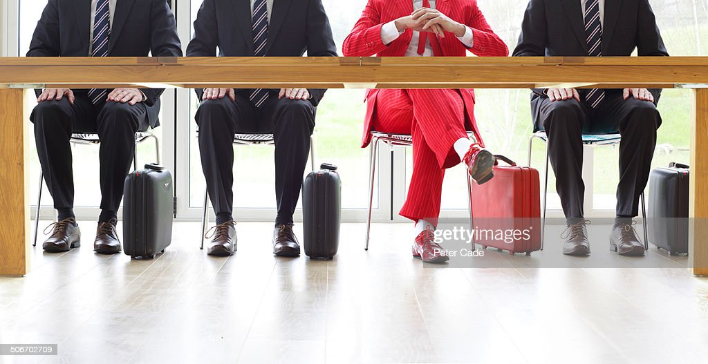 Four men sat at table, one in red suit : Stock Photo