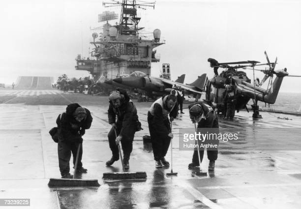 Four men scrubbing the 7000ft long flight deck on HMS Hermes during the Falklands conflict May 1982