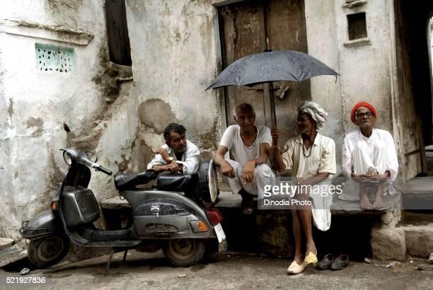 Four Men Sitting in Front of House, Dilwara, Rajasthan, India