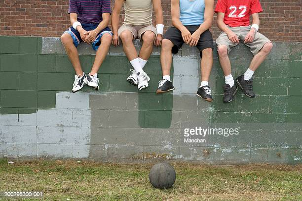Four men sitting on brick wall by basketball, low section
