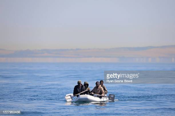 Four men, some using shovels as paddles, use a small dinghy to cross the English Channel on August 7, 2020 off the coast of France. Hundreds of...