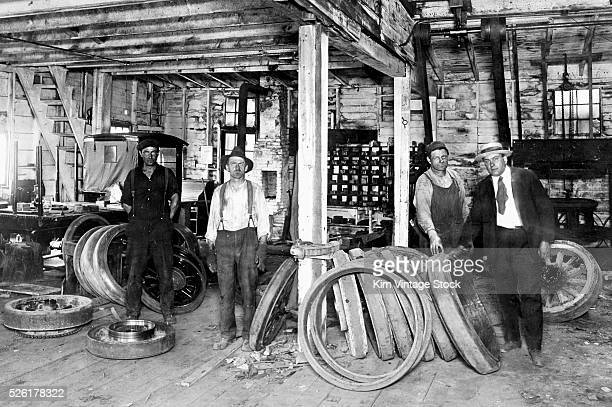 Four men stand in an automotive shop that makes wheel rims