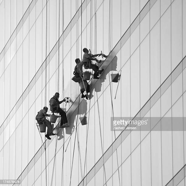 Four men suspended on ropes wash the glass on a tall office building.