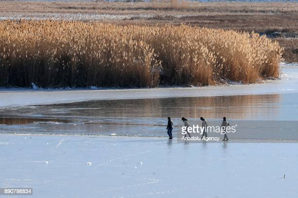 Four men walk on Lake Van as they head to take advantage of frozen surface to fish in Van Turkey on December 12 2017 Hunters dig a hole by breaking...