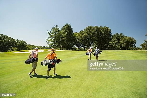 Four men walking across golf course