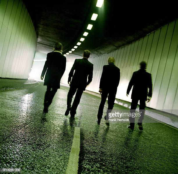 four men walking through tunnel towards exit, rear view - organized crime stock pictures, royalty-free photos & images