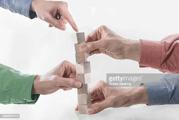 Four men's hands stacking wooden building blocks, Bavaria, Germany