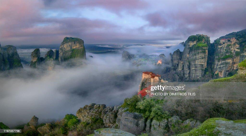 Four Meteora monasteries in mist panorama : Stock Photo