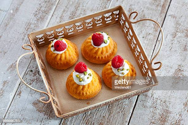 Four mini Gugelhupf filled with cream cheese and ricotta garnished with raspberry and pistachio on tray