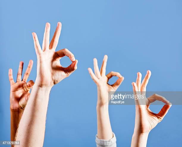 four mixed hands signalling ok with gestures against sky blue - gebaren stockfoto's en -beelden