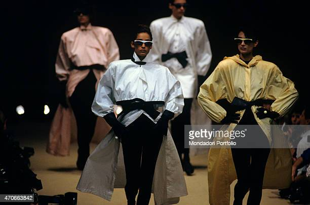 Four models walk down the catwalk with black gloves and sunglasses wearing solid colour coats by the designer Complice Milan 1986
