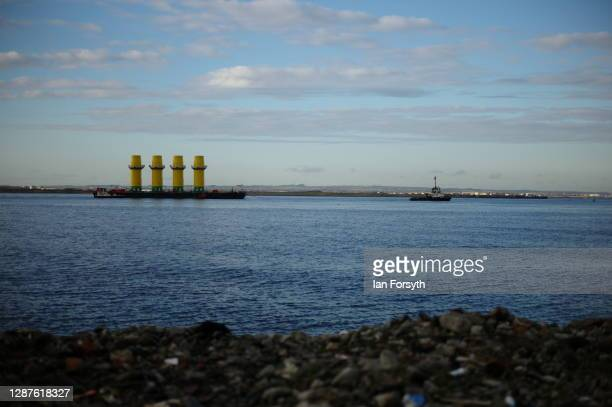 Four monopile structures used as the foundation of wind turbines are transported on a barge towed by a tug boat out of the mouth of the River Tees on...