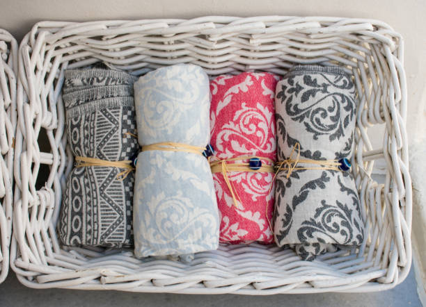 Four multi colored small towels in a white straw basket. The towels are rolled and tied up.