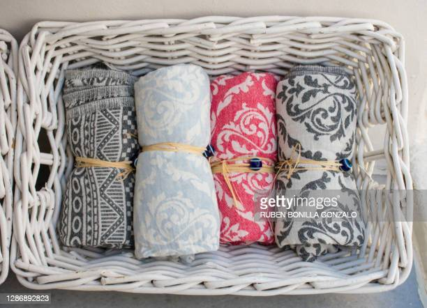 four multi colored small towels in a white straw basket. the towels are rolled and tied up. - gymnastique douce photos et images de collection