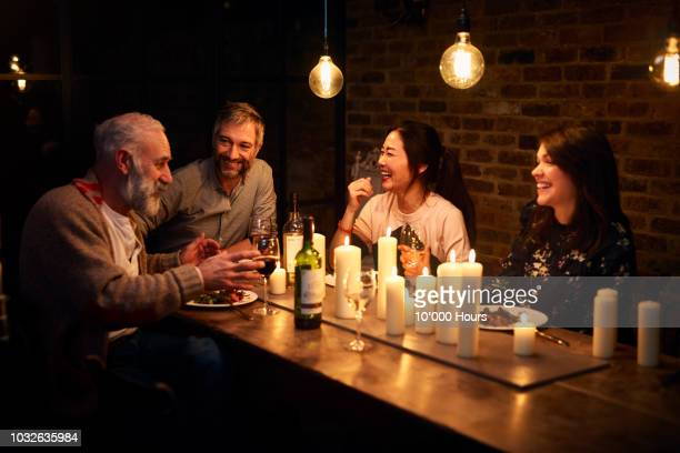 four multi racial friends sitting at dinner and having conversation - warmes abendessen stock-fotos und bilder