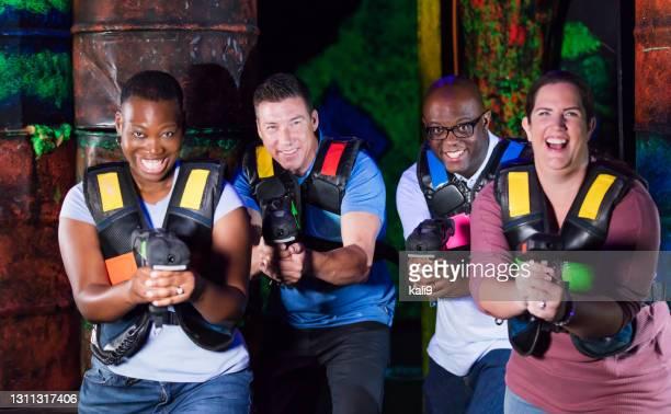 レーザータグを演奏する4人の多民族成人 - 鬼ごっこ ストックフォトと画像