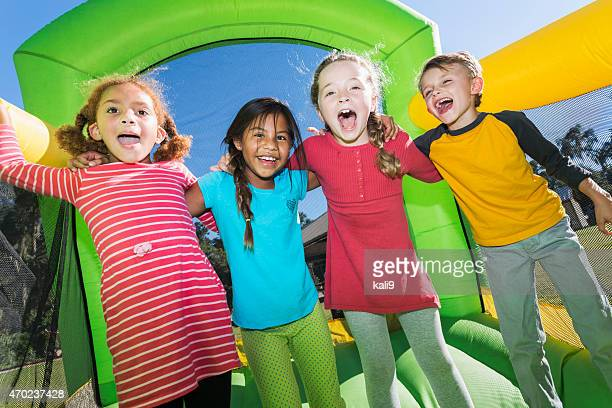 four multi-ethnic children playing on bouncy castle - fete stock photos and pictures