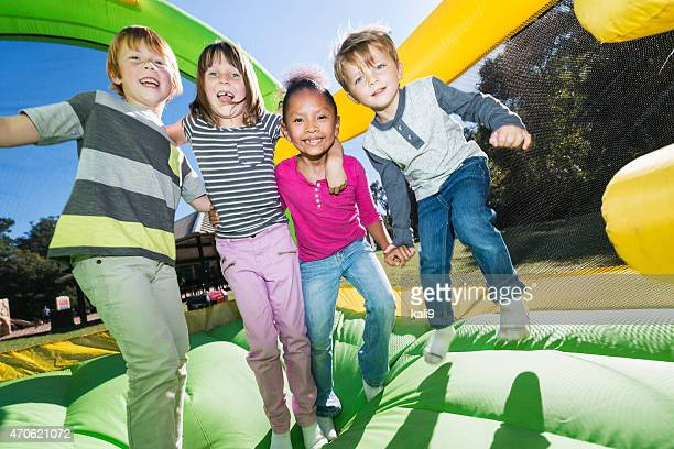 four multi-ethnic children playing on bouncy castle - castle stock pictures, royalty-free photos & images