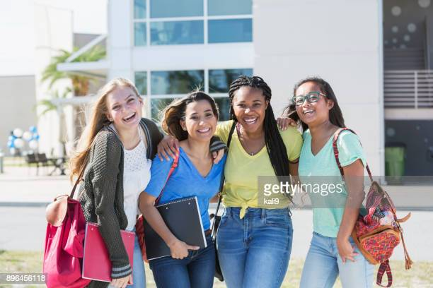 four multi-ethnic teenage students on campus - female high school student stock pictures, royalty-free photos & images