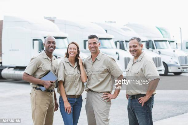 Four multi-ethnic workers in front of semi-trucks