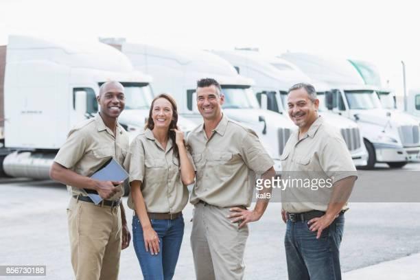 cuatro trabajadores multiétnicos delante de semirremolques - camioneros fotografías e imágenes de stock