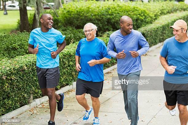 Cuatro multirracial hombres trotar en el parque