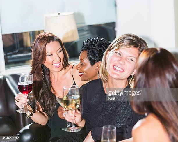 Four multiracial women at a party talking and drinking