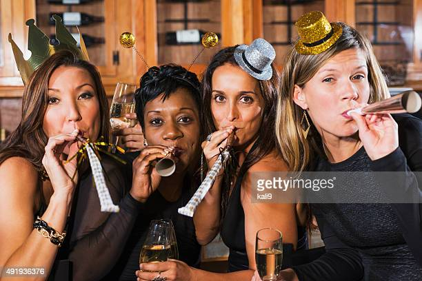 Four multiracial women at a party with champagne