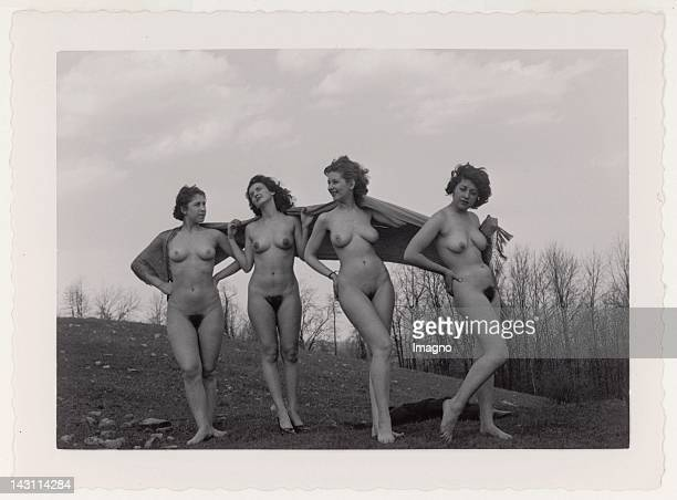 Four naked young women posing in the landscape with a scarf behind their shoulders USA 1950s