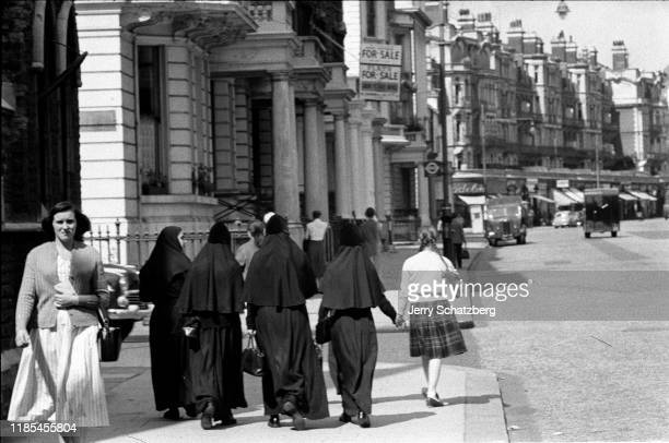 Four nuns in fulllength black habits walk along a street one of whom holds hands with a girl in pigtails London England 1957