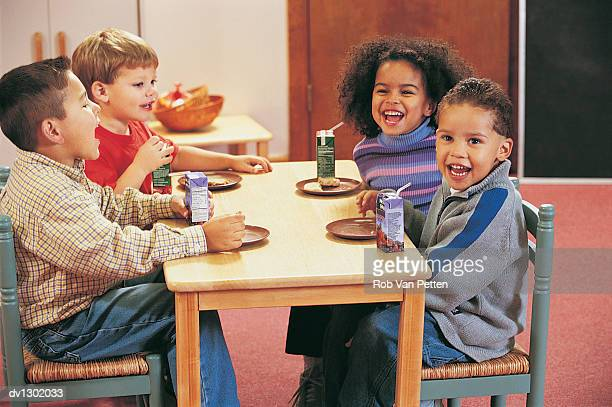 Four Nursery School Children Sitting at a Table for a Snack