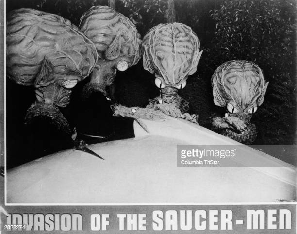 Four of the titular aliens examine the tail fin of a car in a publicity still for 'Invasion Of The SaucerMen' directed by Edward L Cahn 1957