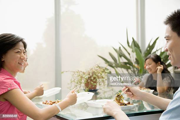 Four office workers having lunch in an office