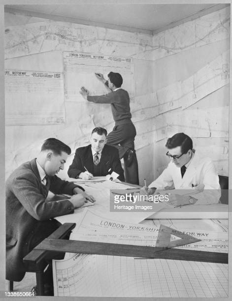 Four office workers, probably at the project headquarters in Newport Pagnell, updating charts and tracking progress in the construction of the London...