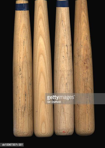 Four old baseball bats on black background