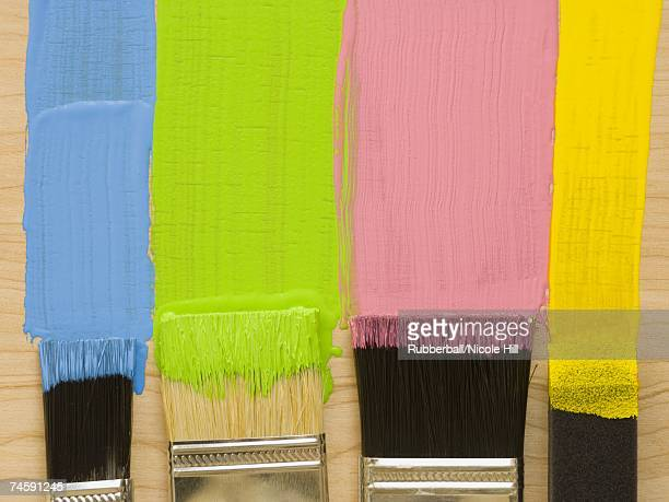 Four paint brushes with stripes of paint