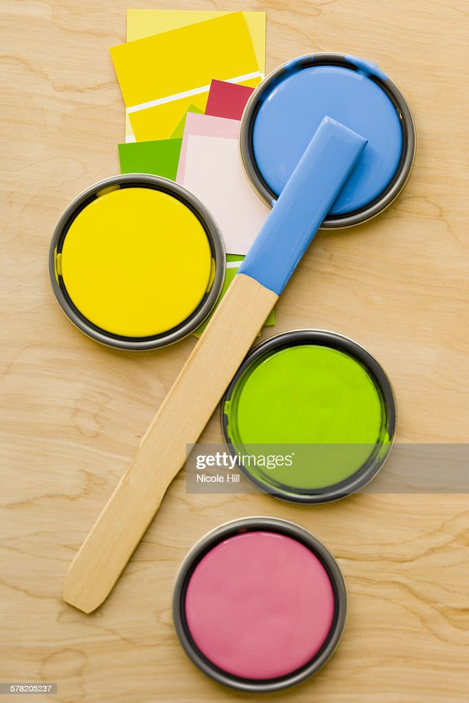Four paint can lids and stir stick from above with paint chips : Stock Photo