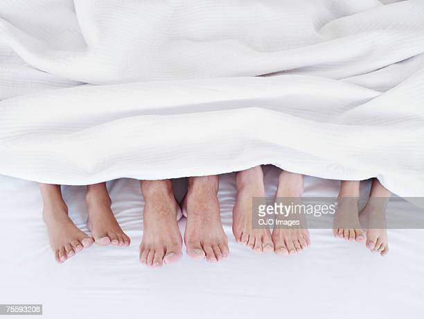 Four pairs of feet protruding out the bottom of a bed sheet