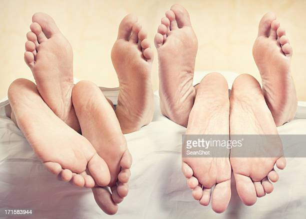 four peolpe in a bed - woman lying on stomach with feet up stock photos and pictures