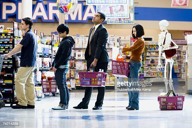 Four people and a skeleton in grocery store lineup