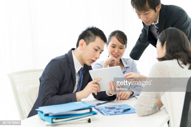four people are watching the tablet and talking with a smile. - initiative stock pictures, royalty-free photos & images