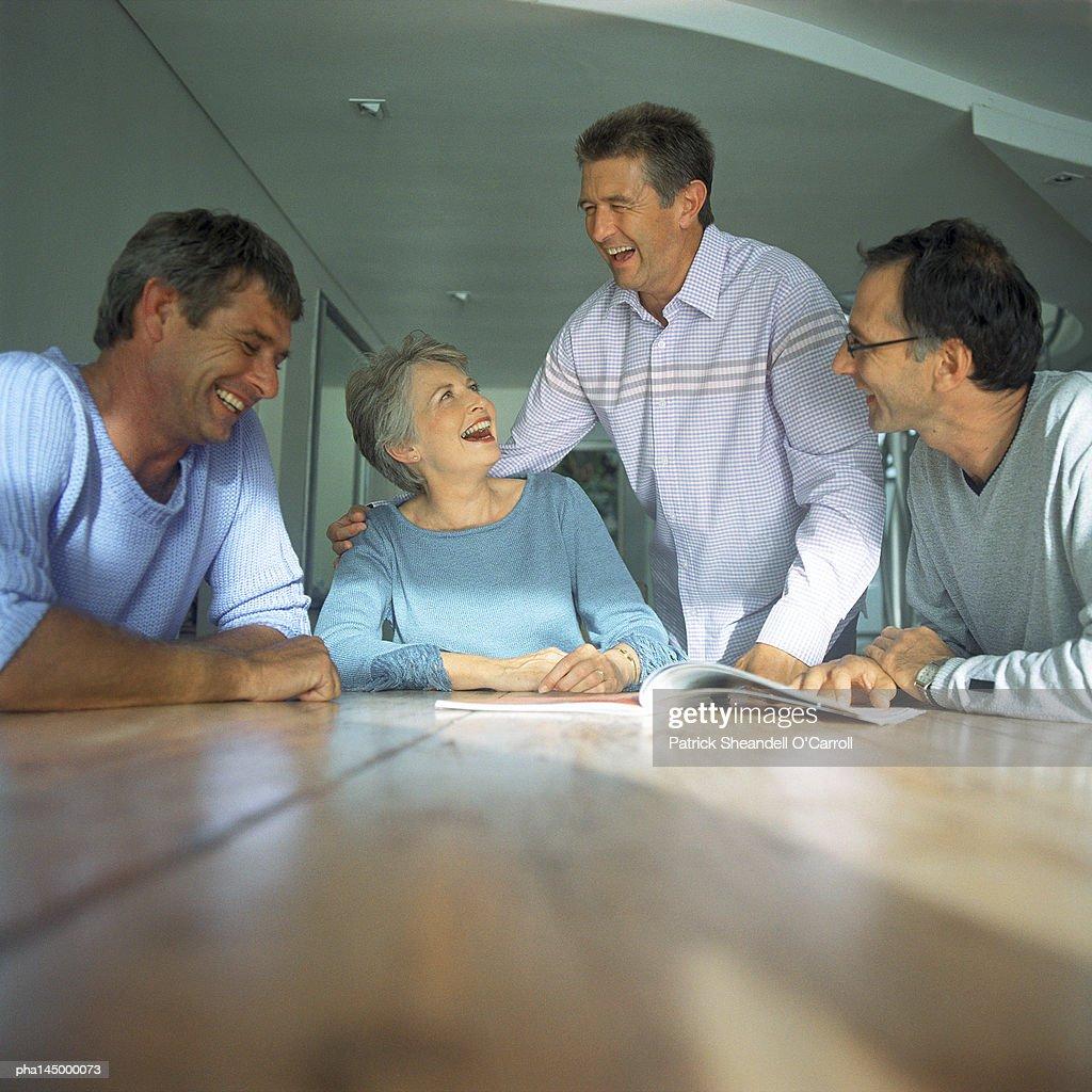 Four people around table : Stockfoto