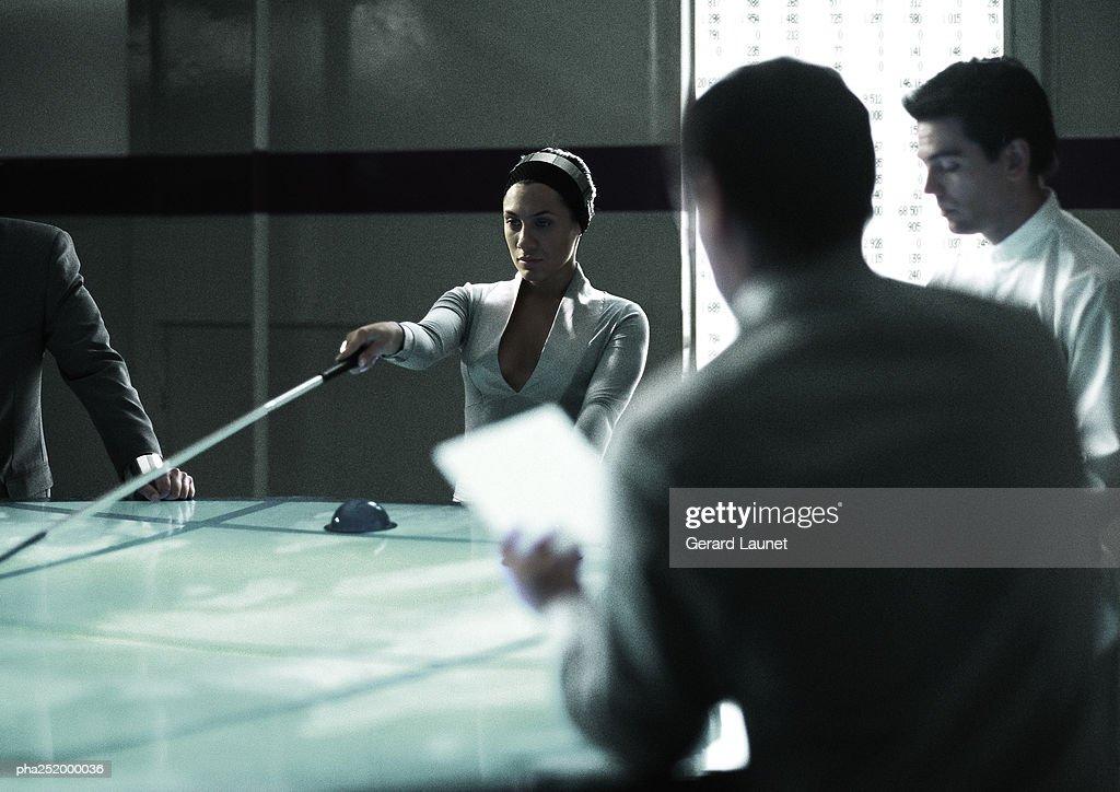 Four people around table, woman holding stick : Stockfoto