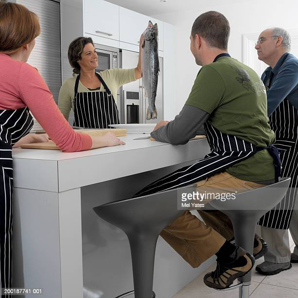 Four people at kitchen counter, mature woman holding up salmon